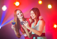 Two girlfriends in a nightclub under the spotlight royalty free stock image