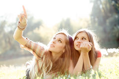 Two girlfriends outdoor looking upwards Royalty Free Stock Photo
