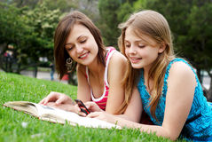 Two girlfriends in park with a mobile phone Royalty Free Stock Image