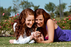 Two girlfriends in park with a mobile phone Royalty Free Stock Photos