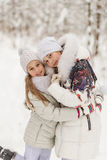 Two girlfriends playing in a winter forest. Royalty Free Stock Image