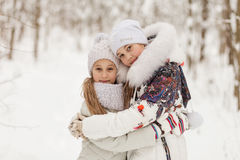Two girlfriends playing in a winter forest. Stock Photos