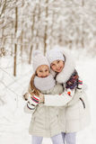 Two girlfriends playing in a winter forest. Royalty Free Stock Photography
