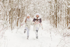 Two girlfriends playing in a winter forest. Stock Photo