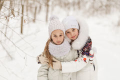 Two girlfriends playing in a winter forest. Stock Images