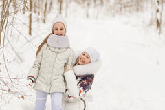 Two girlfriends playing in a winter forest. Royalty Free Stock Photos