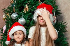 Two girlfriends posing and fooling around the New Year tree near royalty free stock photos