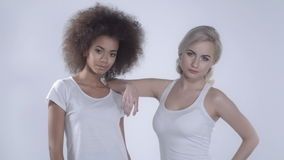 Two girlfriends posing on white background. Two girls in casual clothes over white background stock video