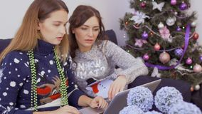 Two girlfriends relaxing at home and makes Christmas purchases in internet. Two young girlfriends in sweaters sits on sofa at home and makes online Christmas stock video