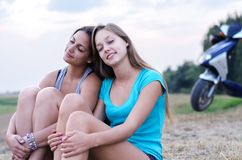 Two girlfriends resting in countryside after riding scooter in s Stock Images
