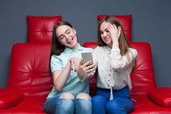 Two girlfriends secretive on red leather couch. Portrait of two attractive girlfriends secretive on red leather couch stock image