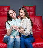 Two girlfriends secretive on red leather couch Royalty Free Stock Photography
