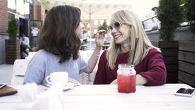 Two girlfriends sharing a secret in an outdoors cafe. Two young friends are sitting in an outside cafe and gossiping. Concept of secret sharing and a small talk stock video footage