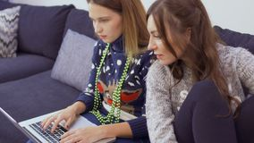 Two girlfriends shopping in the internet at home. Two beautiful girls sits on couch at home and shopping in the internet. Pretty friends are discussing the stock footage