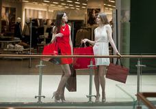 Two girlfriends on shopping walk on shopping centre with bags Royalty Free Stock Photos
