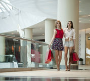 Two girlfriends on shopping walk on shopping centre with bags Royalty Free Stock Image