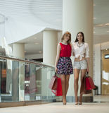 Two girlfriends on shopping walk on shopping centre with bags Stock Images