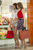 Two girlfriends on shopping walk on shopping centre with bags Royalty Free Stock Photo