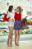 Two girlfriends on shopping walk on shopping centre with bags Stock Photos