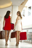 Two girlfriends on shopping walk in shopping mall with bags Royalty Free Stock Photography