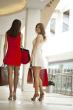 Two girlfriends on shopping walk in shopping mall with bags Stock Images