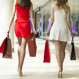 Two girlfriends on shopping walk in shopping mall with bags Stock Photo