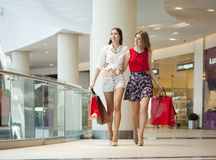 Two girlfriends on shopping walk on shopping mall with bags Stock Photography