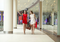 Two girlfriends on shopping walk in shopping mall with bags Royalty Free Stock Photos