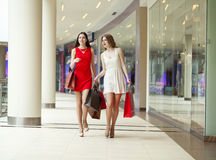 Two girlfriends on shopping walk on shopping mall with bags Stock Photos