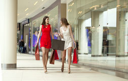 Two girlfriends on shopping walk on shopping mall with bags Royalty Free Stock Photos
