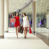 Two girlfriends on shopping walk on shopping mall with bags Stock Image