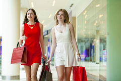 Two girlfriends on shopping walk on shopping mall with bags Stock Images
