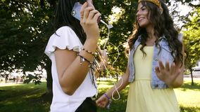 Two girlfriends / sisters dance in pairs and listen to music. Girls listen to music through headphones, sing along and dance. Girls dancing on the grass stock video footage