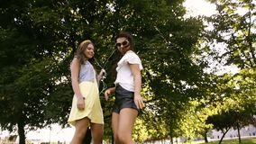 Two girlfriends / sisters dance in pairs and listen to music. Girls listen to music through headphones, sing along and dance. Girls dancing on the grass stock footage