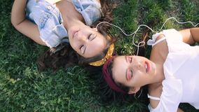 Two girlfriends / sisters are lying on the grass, listening to music on headphones. Two brunettes lie on the grass in the park,. Relax, sing stock video
