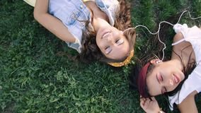 Two girlfriends / sisters are lying on the grass, listening to music on headphones. Two brunettes lie on the grass in the park, stock video footage