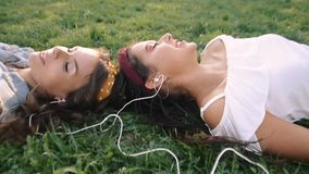 Two girlfriends / sisters are lying on the grass, listening to music on headphones. Two brunettes lie on the grass in the park,. Relax, sing stock video footage