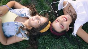 Two girlfriends / sisters are lying on the grass, listening to music on headphones. Two brunettes lie on the grass in the park,. Relax, sing stock footage