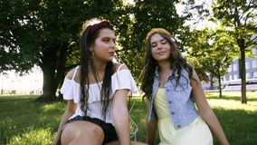 Two girlfriends / sisters are paired and listening to music. Girls listen to music through headphones, sing along and dance. Girls. Are sitting on the grass and stock video