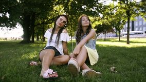 Two girlfriends / sisters are paired and listening to music. Girls listen to music through headphones, sing along and dance. Girls. Are sitting on the grass and stock footage