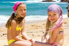 Two girlfriends sitting on beach. Portrait of two kids in swimwear sitting next to sea Royalty Free Stock Images