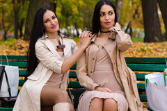 Two girlfriends sitting on bench with shopping. Outdoors Stock Photos