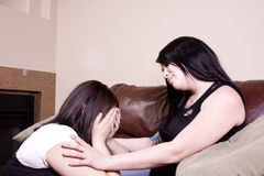 Two Girlfriends Sitting on the Couch. One consoling the other crying girl stock photography