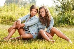 Two girlfriends sitting on grass Stock Photo