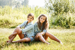 Two girlfriends sitting on grass Royalty Free Stock Photos