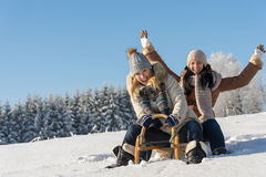 Two girlfriends sledge downhill in wintertime Royalty Free Stock Images