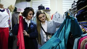 Two girlfriends smiling choose the clothes in the store. Girls choose between red and blue dresses stock video footage