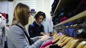 Two girlfriends smiling choose the clothes in the store. They help each other with a choice stock video