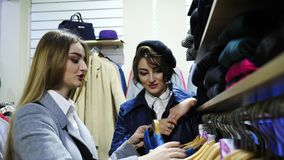 Two girlfriends smiling choose the clothes in the store. They help each other with a choice stock footage