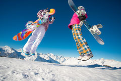 Two girlfriends snowboarders jumping in the alpine mountains. Stock Photography